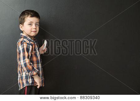 Cute little boy next to a chalkboard