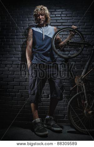 Portrait of guy with bicycle standing against brick wall