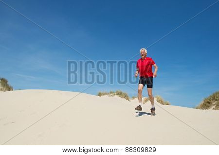 Senior runner in nature dunes