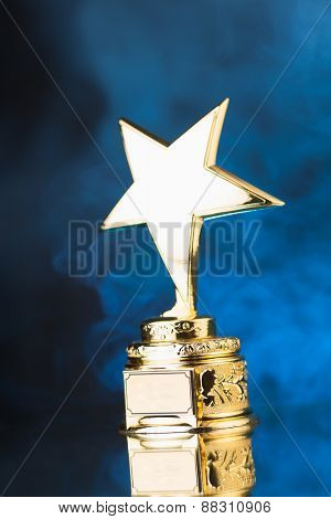 gold star trophy against blue smoke background