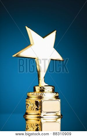 gold star trophy against blue background