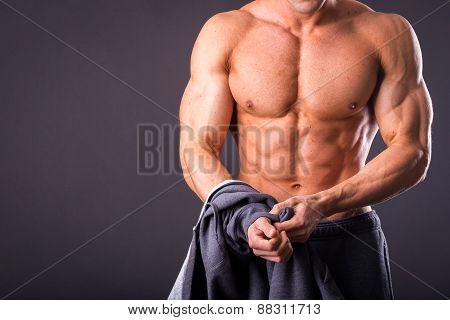 A man shows his abdominal muscles, raised his hand t-shirt