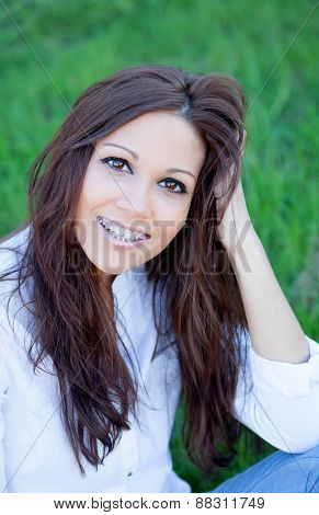Brunette cool girl with brackets sitting on the grass