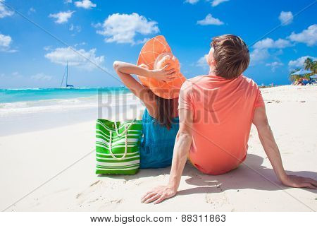 happy young couple sitting on a tropical beach in Barbados