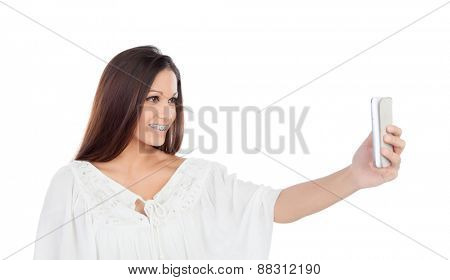Attractive casual girl taking a photo with her mobile isolated on a white background