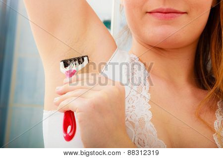 Woman Shaving Armpit With Razor In Bathroom