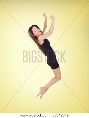 Happy young girl jumping with a short dress on a yellow background