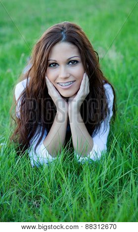 Brunette cool girl with brackets lying on the grass