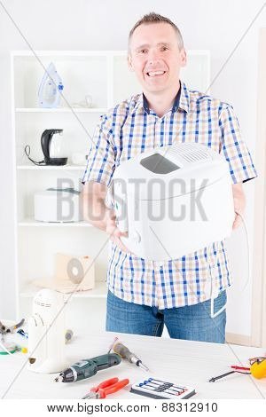 Smiling man holding repaired deep fryer at home appliance service workshop