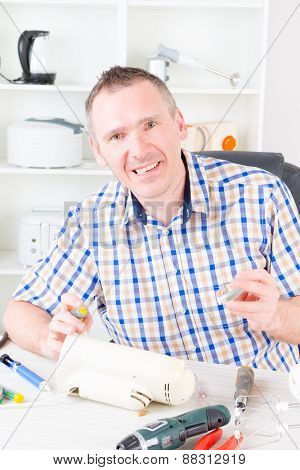 Smiling man repairing electric can opener at home appliance service workshop