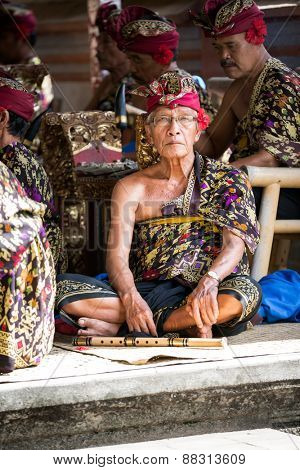 BALI, INDONESIA, DECEMBER, 24,2014: senior musician sitting on floor with his  group musicians and looking at camera Barong Dance show on December 24, 2014 in Bali, Indonesia