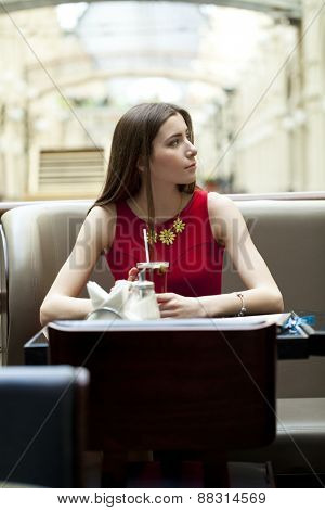 Beautiful young brunette woman sitting in a coffee shop and drink tea