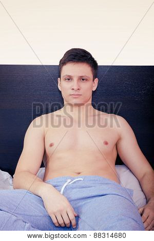 Satisfied Pensive Shirtless Man In Bedroom