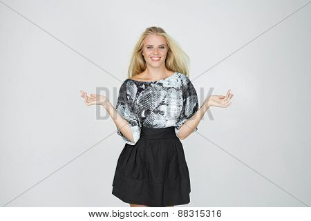 Half-length portrait of beautiful smiling blonde wearing blouse and black skirt standing aside pointing out something looking at us. Isolated on gray background