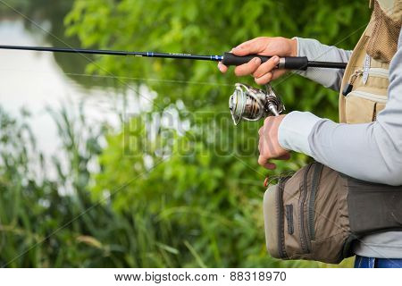 Fishing in river. A fisherman with a fishing rod on the river bank.
