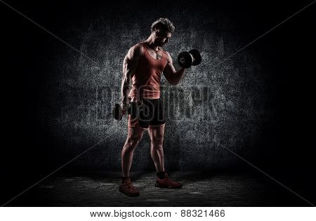 Muscular Male Athlete Is Training By Lifting Dumbbells
