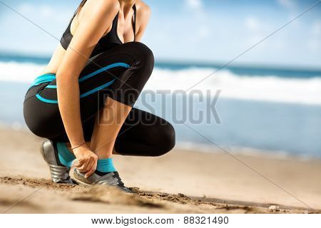 woman in sports clothes tying shoelaces before running on beach