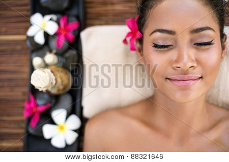 Serene beautiful spa woman relaxing on massage desk