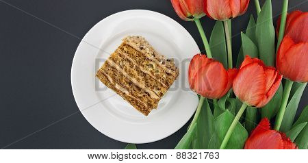Cake Slice With Nut On Plate. Bouquet Of Tulips. Top View