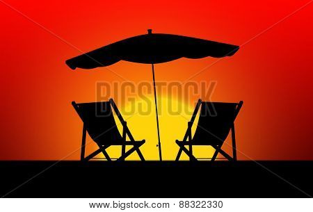 Two sun loungers and parasols at sunset