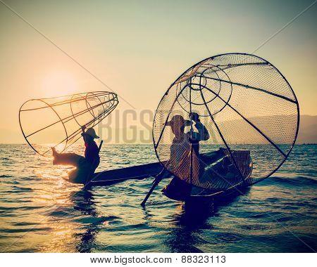 Myanmar travel toursist attraction landmark - two traditional Burmese fishermen at Inle lake, Myanmar on sunrise. Vintage filtered retro effect hipster style image