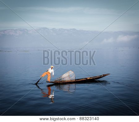 Traditional Burmese fisherman rowing on one leg at Inle lake, Myanmar famous for their distinctive one legged rowing style. Vintage filtered retro effect hipster style image
