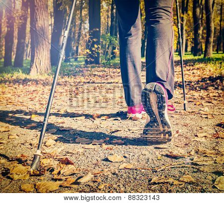 Close up of hinking woman feet and nordic walking poles. Vintage retro effect filtered hipster style image