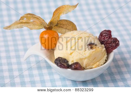 A scoop of homemade cranberry ice cream with physalis and dried cranberries