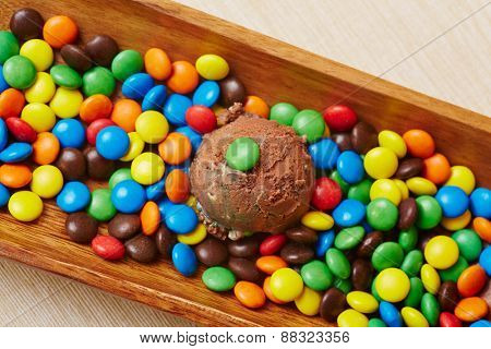 Scoop of chocolate ice cream with many colorful chocolate beans