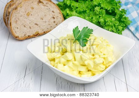 Egg Salad In A Bowl With Bread And Lettuce On Background