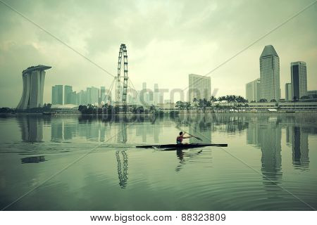 Singapore skyline with urban buildings and boat reflection over water