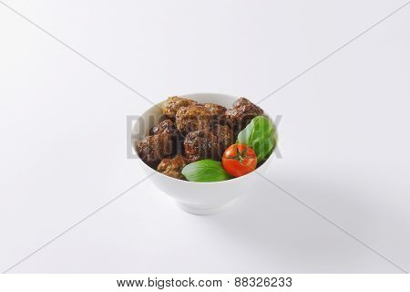 bowl of fresh meatballs, cherry tomato and basil on white background