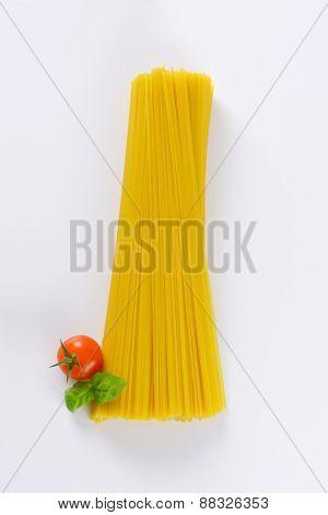 uncooked spaghetti, cherry tomato and basil on white background