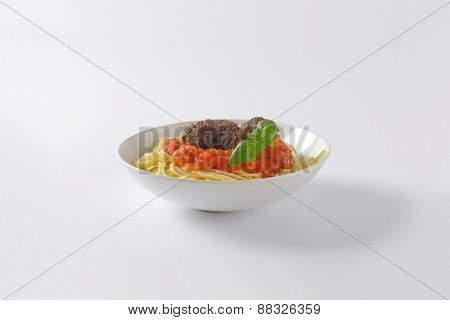 plate of spaghetti and meatballs in tomato sauce on white background