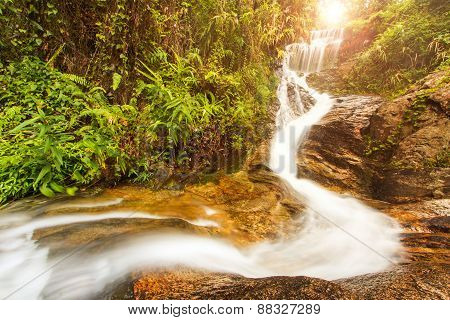 Tropical Waterfall In Rainforest With Sunray