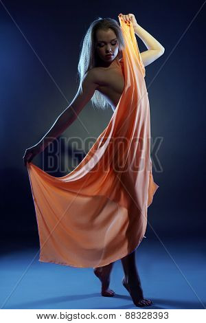 Nude girl dancing with cloth in ultraviolet light