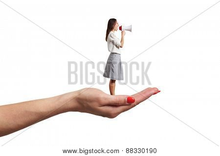 big palm holding small screaming woman with megaphone. isolated on white background