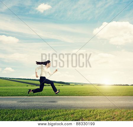 businesswoman in formal wear running fast on the road at outdoor against the background of beautiful scenery