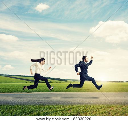 man and woman in formal wear running fast on the road at outdoor against the background of beautiful scenery