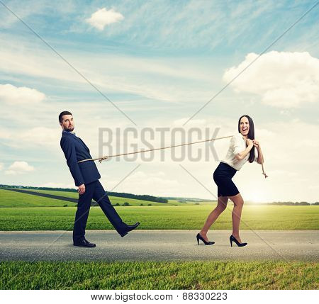 concept photo of henpecked husband. happy laughing woman pulling man on the rope at outdoor