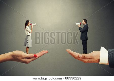 man and woman standing on the big palms and screaming at each other over dark background