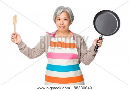 Old woman hold up with wooden ladle and fried pan