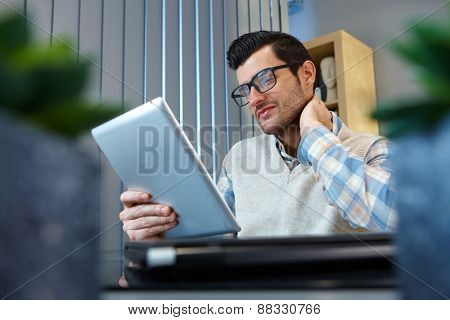 Businessman reading e-book at home.
