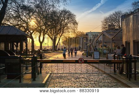 LONDON, UK - APRIL15, 2015: Tower park in sun set. River Thames side walk with people resting by the