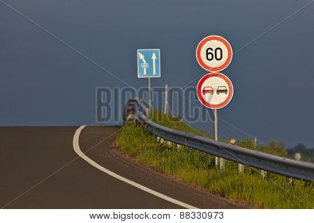Traffic signs on the side of a road with stormy sky background