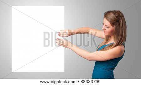 Pretty young woman presenting white paper copy space