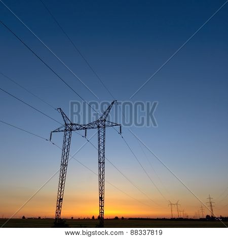 Large transmission towers at blue hour