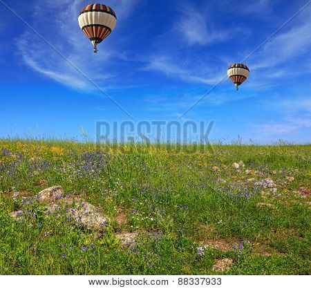Two huge and beautiful balloons fly over a flowering field. Flowering Golan Heights on a sunny day