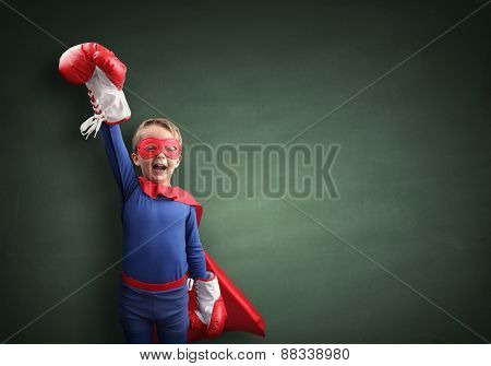 Superhero child winner with boxing gloves concept for winning, childhood, imagination, aspirations and strength