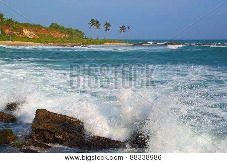 Large ocean waves breaking on the rocks of tropical coast